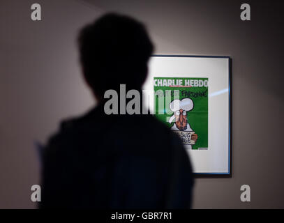 Hanover, Germany. 8th July, 2016. A man standing in front of the 14.01.2015 title page of the French satirical magazine - Stock Photo