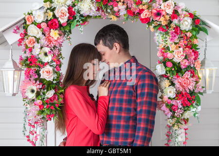 Loving couple hugging, sitting on the porch, decorated with a floral composition. Provence, spring. - Stock Photo