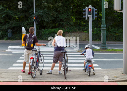 family people waiting cross road bikes bicycles - Stock Photo