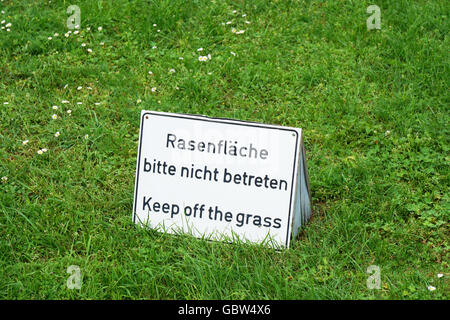 bilingual keep of the grass sign in Germany - Stock Photo