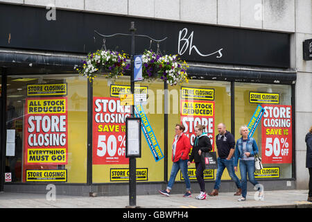 Shoppers passing British Home Stores shop in Truro, Cornwall with closing down sale notices in the windows. - Stock Photo