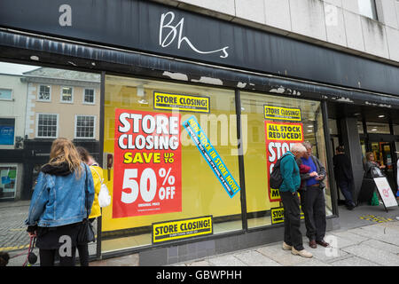 Shoppers outside British Home Stores shop in Cornwall, England, with closing down sale posters. - Stock Photo