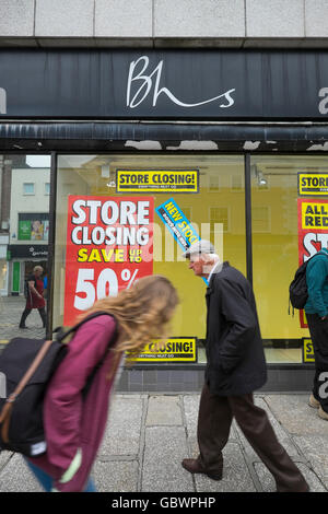 Shoppers passing British Home Stores shop in Truro, Cornwall, with closing down notices in the windows. - Stock Photo