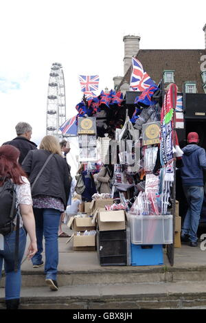 Curio sellers at their stall on Westminster Bridge with the London Eye in the background - Stock Photo