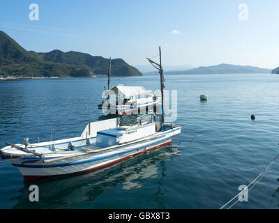 Two wooden fishing boats moored in the Seto Inland Sea. - Stock Photo