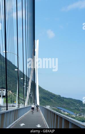 Two cyclists crossing the Tatara Bridge connecting the islands of Omishima and Ikuchi in the Seto Inland Sea. - Stock Photo