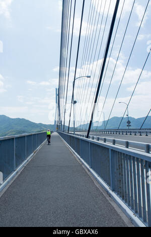 A cyclist cycling on the bicycle lane on theTatara Bridge connecting the islands of Omishima and Ikuchi in the Seto - Stock Photo