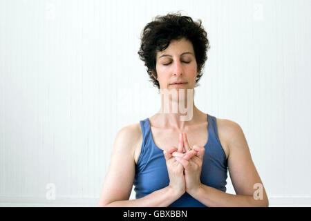 Woman doing yoga in a studio. Pose: 'Devi mudra'. - Stock Photo