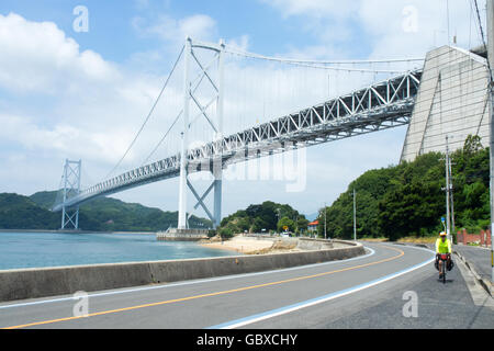 A cyclist cycling under the Innoshima Bridge connecting the islands of Innoshima and Mukaishima in the Seto Inland - Stock Photo