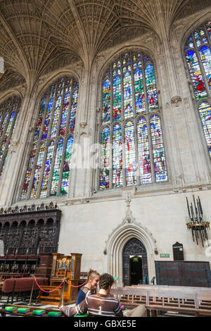 England, Cambridgeshire, Cambridge, King's College Chapel, Couple and Stained Glass Windows - Stock Photo