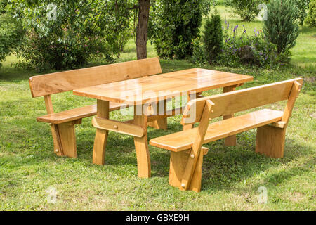 Wooden set of table, benches with backrests on green grass lawn. Vacation place in garden. Summer leisure time. - Stock Photo