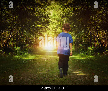 A child is walking in the dark woods into a bright light on a path for a freedom or happiness concept. - Stock Photo