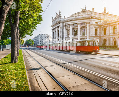 Wiener Ringstrasse with historic Burgtheater (Imperial Court Theatre) and traditional  electric tram at sunrise, - Stock Photo