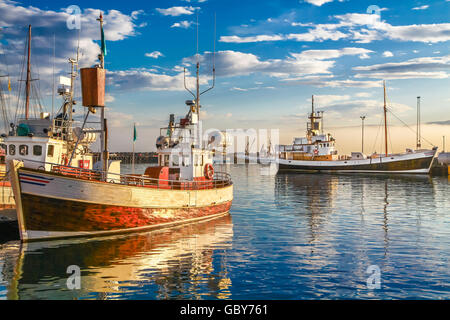 Traditional old wooden fisherman boats lying in the harbor of Husavik in beautiful golden evening light at sunset, - Stock Photo