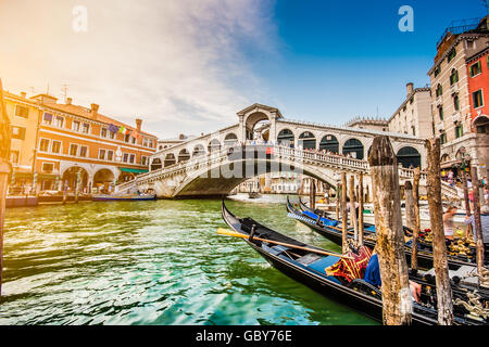 Classic view of traditional Gondolas on famous Canal Grande with famous Rialto Bridge at sunset in Venice, Italy - Stock Photo