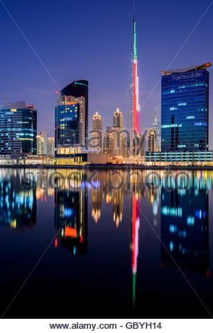 Burj Khalifa lit up with the UAE Flag reflecting on the lakes, Dubai Downtown, United Arab Emirates - Stock Photo
