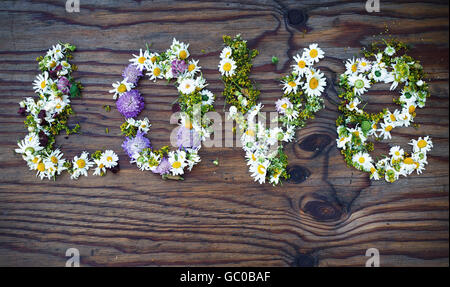 Inscription LOVE made of flowers and leaves on vintage wooden table background. Word love made of flowers.Top view. - Stock Photo