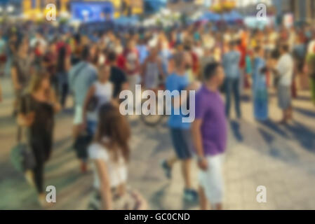 Blur street crowd in summer evening, out of focus unrecognizable people walking in urban environment - Stock Photo