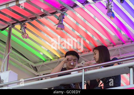 Couple eating Snog frozen yoghurt on pink Snog bus at South Bank, London in July - Stock Photo
