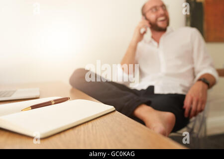 Diary on desk with man sitting in background talking on mobile phone. Businessman working from home office. - Stock Photo