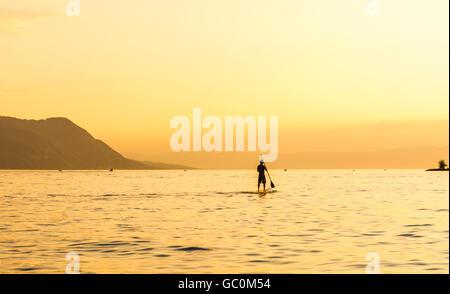 A single paddle boarder on Lake Geneva in Switzerland at sunset - Stock Photo