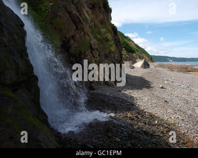Waterfall on to the beach at Bucks Mill, Devon, UK - Stock Photo