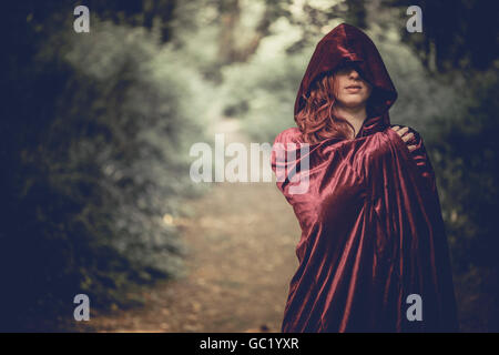 Woman of mystery: A young red haired redhead woman girl wearing a cape, obscuring her face, alone in a forest - Stock Photo