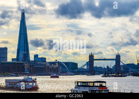 London cityscape with Tower Bridge against a sky with dramatic clouds - Stock Photo