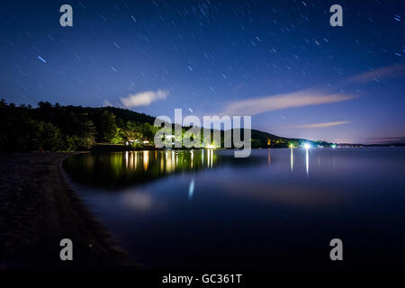 Long exposure of stars moving over Lake Winnipesaukee at night, at Ellacoya State Park, in Laconia, New Hampshire. - Stock Photo