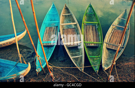 Group of colorful rowing boat anchor on day, abstract curve of bamboo boat in vintage colors, stakes on mud - Stock Photo