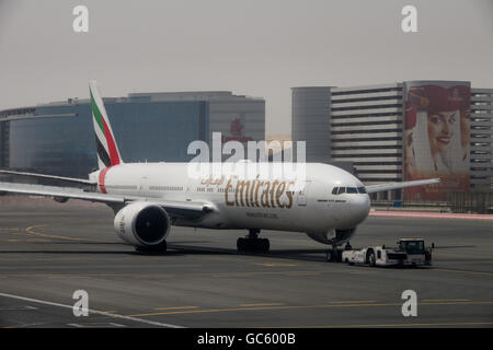An Emirates Boeing 777-300ER pushes back from the gate at Dubai International Airport - Stock Photo