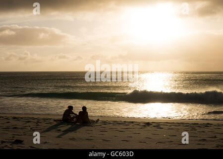 A couple relax on a beach on Praslin Island, Seychelles - Stock Photo