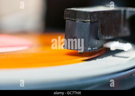 stylus of headshell on orange vinyl record close up - Stock Photo