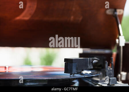 side view of headshell of old turntable with stylus on vinyl record - Stock Photo