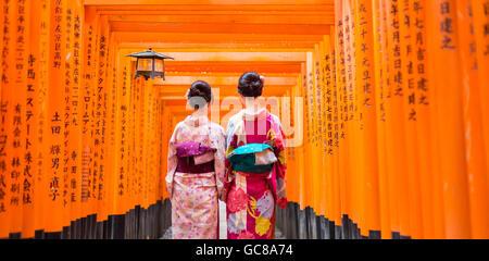 Two geishas among red wooden Tori Gate at Fushimi Inari Shrine in Kyoto, Japan - Stock Photo
