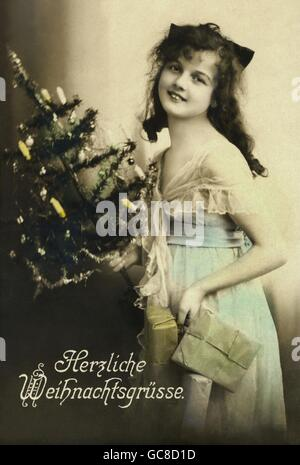 Christmas, woman with Christmas tree and presents, 'Herzliche Weihnachtsgruesse' (Merry Christmas), Germany, 1920, - Stock Photo