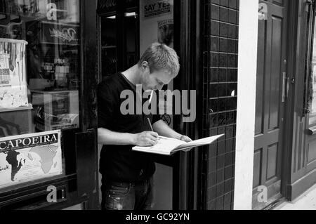 An artist drawing in his pad whilst smoking - Stock Photo