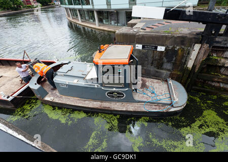Bantam tug Ilda leaving City Road Lock, on the Regents Canal, pushing two barges in front of it - Stock Photo