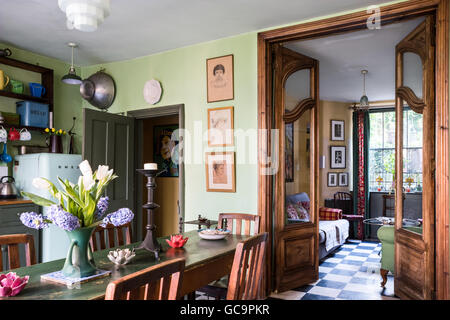 Oak dining chairs with view through double doors to sitting room in Nottinghill Victorian terrace, London, UK - Stock Photo