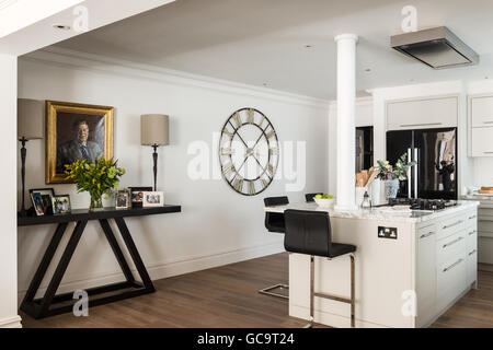 Family photos on a console table by John Chichester in open plan kitchen with large wall clock - Stock Photo