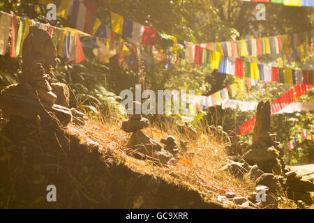 Buddhist prayer flags and stacked religious stones arranged at Khecheopalri Lake, Pelling, Sikkim, India - Stock Photo