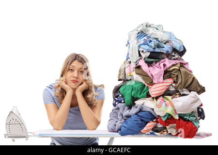 Sad woman posing next to a pile of clothes for ironing isolated on white background - Stock Photo