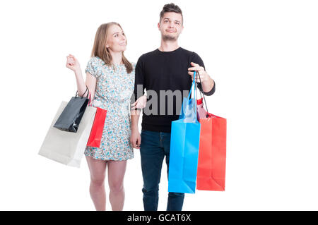 Young happy couple relaxing and doing shopping in their leisure isolated on white background - Stock Photo