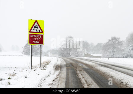 A slippery surface warning road sign on the side of a rural road while it is snowing with snow on the ground. - Stock Photo