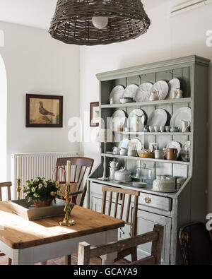 Irish open shelf dresser in dining area with basket lampshade by Leroy Merlin - Stock Photo