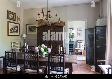 18th century oak table and Yorkshire chairs in dining room with terracotta flooring, painted Austrian cupboard and - Stock Photo