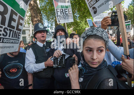 London, UK. 8th July 2016. A police officer holds a pro-Israel protesters who is wearing Palestinian scarf from - Stock Photo