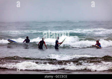 A group of surfers waiting in the sea to catch and wave for surfing at the popular surfing beach at Freathy, Whitsand - Stock Photo