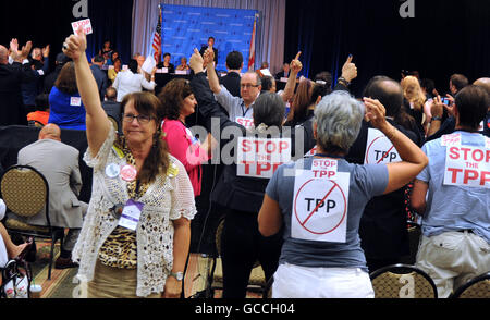 Orlando, Florida, USA. 9th July, 2016. Opponents of the Trans-Pacific Partnership (TPP) stand and raise their hands - Stock Photo