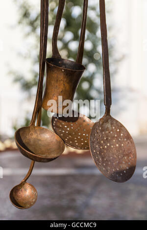 Old copper kitchen utensils hanging in the window. - Stock Photo
